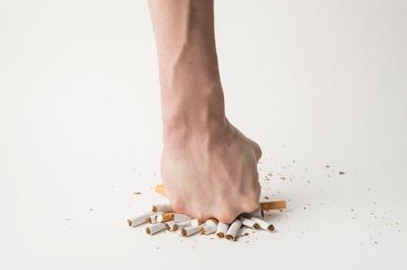 mano hombre rompiendo cigarrillos